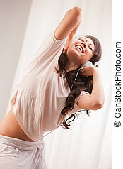 girl listening to music in her house dancing and singing...