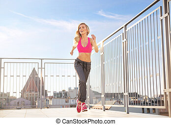 Charming, athletic woman running on the roof