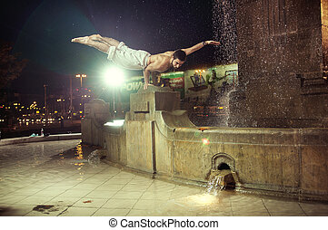 Fit guy doing push-ups in a fountain