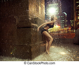 Fit woman making a figure in a fountain