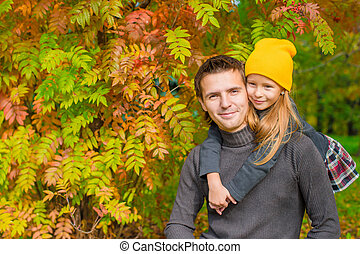 Father with cute daughter in autumn park outdoors - Young...