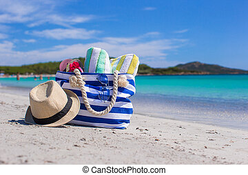 Blue bag, straw hat, flip flops and towel on white tropical beach