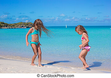 Little girls enjoy their summer vacation on the beach -...
