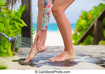 Young woman washes the sand from her feet on white beach -...