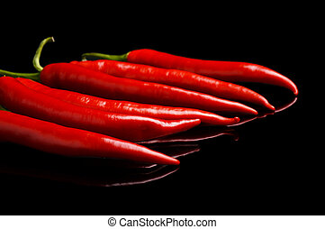 Perspective view of red peppers isolated black background -...