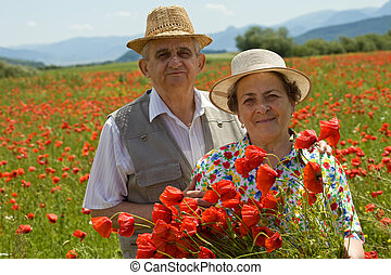 Senior couple on the poppy field enjoying summer - Contented...