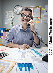 Nerd office worker on the phone sitting at desk and smiling.