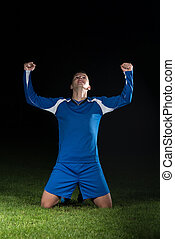 Soccer Player Celebrating The Victory On Black Background