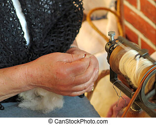 elderly woman works the wool with an antique spinning wheel