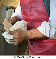 senior artisan washes his hands after work in the handicraft...