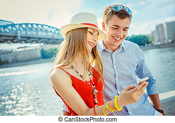 Vacations - Young couple with mobile phone