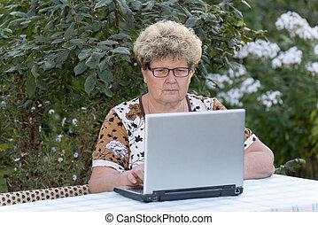 elderly woman working on computer in the garden - elderly...