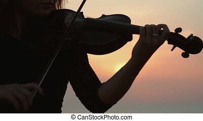 Beautiful girl playing the violin while the sun sets in the...