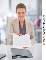Closeup on happy business woman giving document