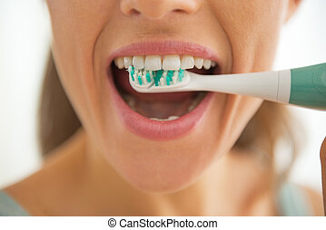 Closeup on woman brushing teeth