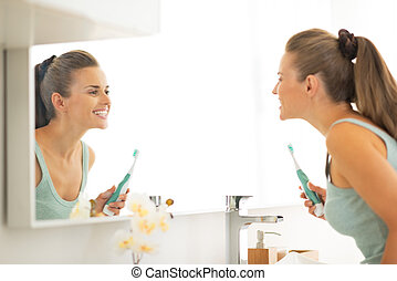 Young woman looking in mirror after brushing teeth