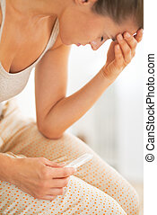 Concerned young woman with pregnancy test