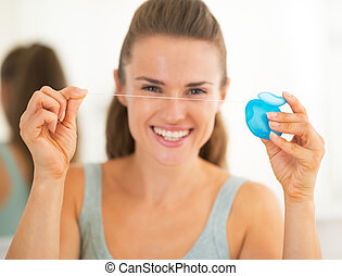 Closeup on happy young woman showing dental floss
