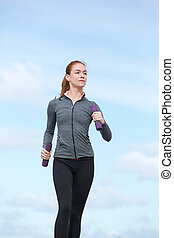 Young woman keeping fit by power walking - Active young...