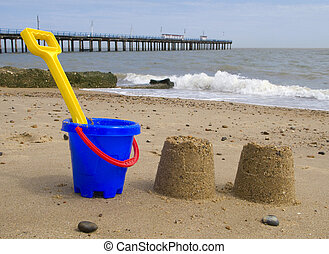 Kids bucket, spade and sandcastles on Felixstowe beach.