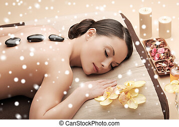woman in spa salon with hot stones - beauty, health,...