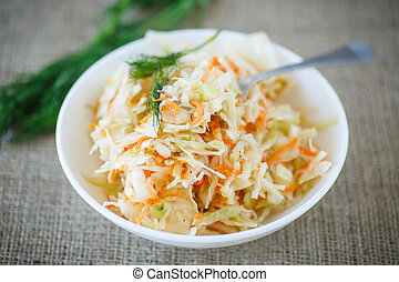 sauerkraut - pickled cabbage and carrots in a white plate on...