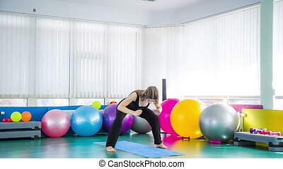 Young Girl Stretching Body In the Gym - Young girl is...