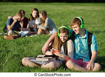 Friends Listening to MP3 Player - Teen students sitting and...