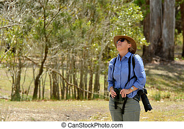 Mature woman birdwatching watching with binoculars in...