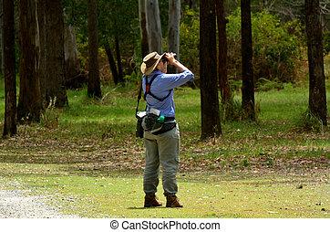 Mature woman birdwatching watching through binoculars in...