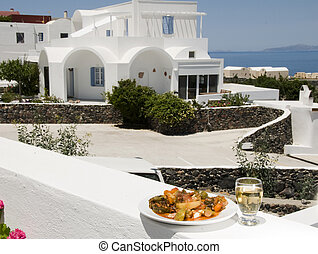 mixed vegetables and white wine at greek island santorini taverna restaurant with view of classic cyclades architecture and the mediterranean sea