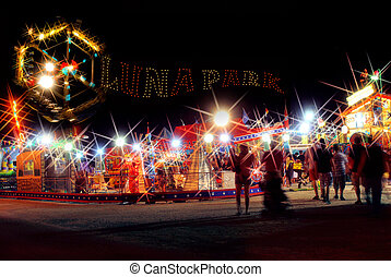 Fairground. - Brightly lit fairground with intentional...