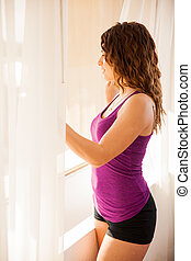Sexy brunette next to a window