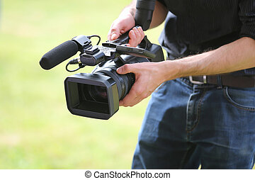 Video camera man with camera on green background