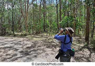 Mature woman birdwatching watching through binoculars in...