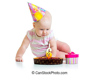 baby girl looking at birthday cake