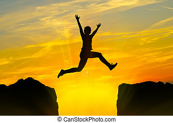 Young person jumping over the mountains - Silhouette of...