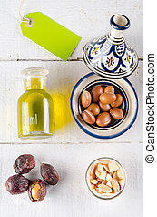 Argan nuts and oil on white wooden tabletop with green label...
