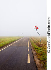 Foggy empty rural road with danger sign