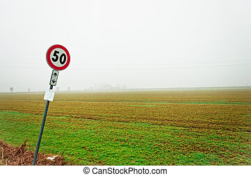 Foggy empty rural road with sign