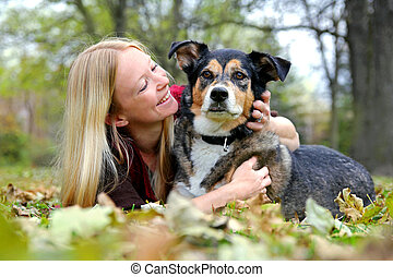 Woman Relaxing with her German Shepherd Dog on Fall Day - a...