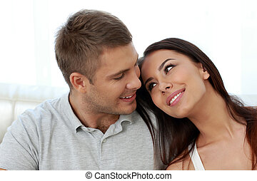 Smiling couple sitting on the sofa together