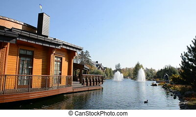 The fountain and wooden house in Mezhigirya, Ukraine It is...