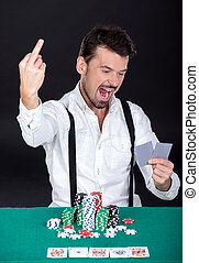 Poker - Happy man is playing poker in casino. Gambling chips...