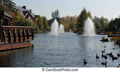 The fountain and wooden house in Mezhigirya, Ukraine. It is...