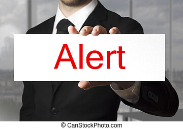 businessman holding sign alert - businessman in black suit...
