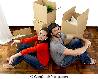happy couple moving together in a new house unpacking...