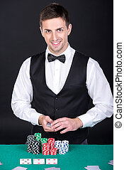 Poker - Portrait of a happy croupier is holding playing...