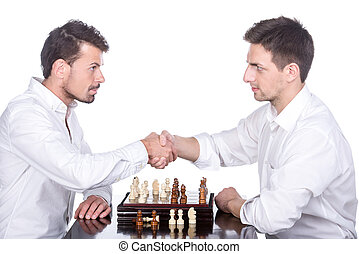 Chess - Shaking hands of two men are playing chess on the...