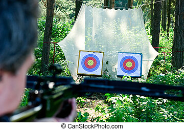 Crossbow shooting - Man aiming crossbow at targets in summer...